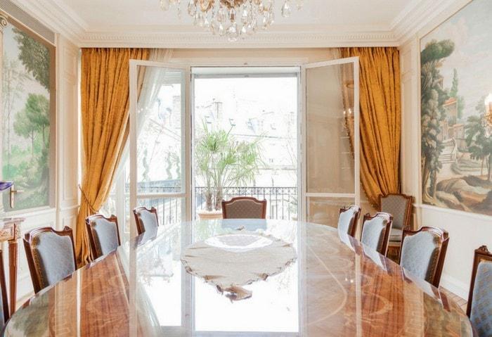 Классический дорогой ремонт столовой в светлых цветах, большой обеденный стол из дорогих пород дерева, оригинальные картины на стенах, выход на балкон