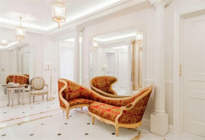 Светлый дорогой ремонт прихожей, монохромная белая отделка с ярким красным классическим диваном