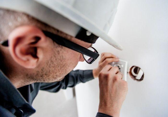 Электрик подключает новые розетки