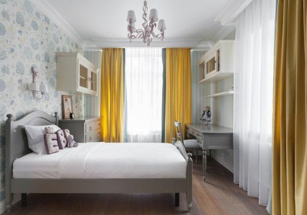 Комфортный ремонт детской комнаты для девочки, три стены оклеены сдержанными обоями с вертикальными полосками, для четвёртой стены выбраны интересные обои с цветочной тематикой, яркие жёлтые обои выгодно распределяют внимание