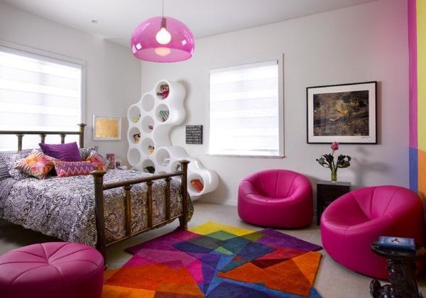 Базовый ремонт комнаты выполнен в белом, одна из стен выкрашена в контрастные яркие цвета (розовый, синий, жёлтый, оранжевый), вся мебель и декор в дальнейшем подбиралась под яркую стену