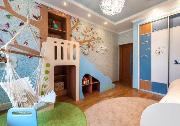 Интересный вариант организации зоны активности в комнате девочки: у стены организовали горку, под ней - полочки для игрушек, рядом - удобное подвесное кресло