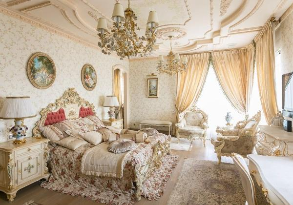 Светлая спальная комната в стиле Барокко, цветочный декор, множество мягких подушек, две хрустальные люстры под потолком