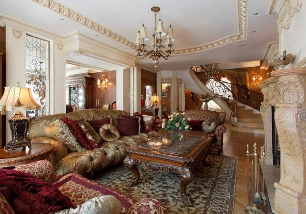 Просторная гостиная в стиле Барокко, винтажный стол из тёмного дерева с резными ножками, винтажные же диван и кресла, мраморный камин