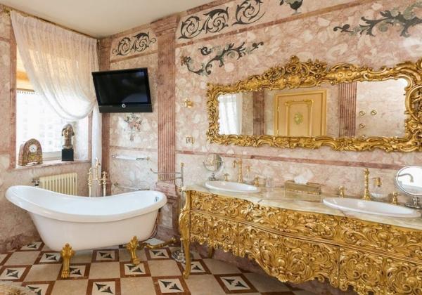 Современная ванная комната в стиле Барокко, основное внимание к себе приковывает оформление двух раковин, позолоченная мебель сочетается такими же ножками ванной