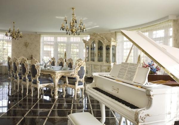 Просторная столовая в стиле Барокко в загородном доме, широкий стол, стулья с изысканными резными спинками, резная мебель в тон, интерьер дополняет белый классический рояль