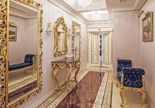 Коридор в стиле Барокко, оформленный дорогой плиткой из натурального камня, декорирован мебелью с резными ножками и сразу тремя большими зеркалами в массивных резных рамах