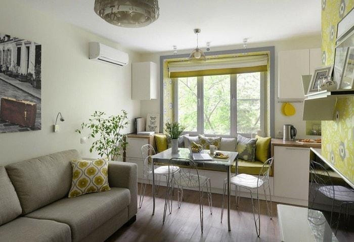 Оригинальное использование характерных высоких окон, под ними оформлен мягкий диванчик и небольшой обеденный стол