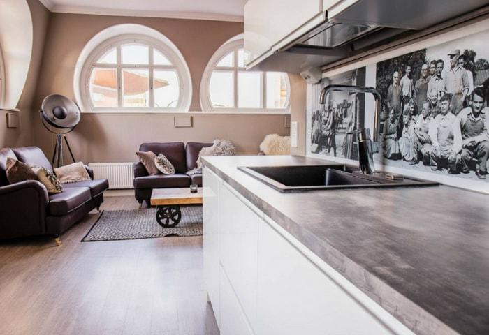 Кухня в сдержанном стиле Модерн, деревянный пол, кожаные диваны, круглые окна