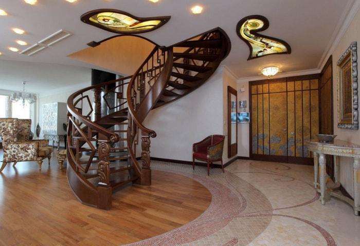 Широкая спиральная лестница и витражные вставки с подсветкой в потолке