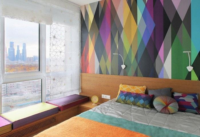 Низкое окно в маленькое спальне переоборудовано в удобное место для отдыха, контрастная стена с геометрическим рисунком выгодно разбавляет атмосферу
