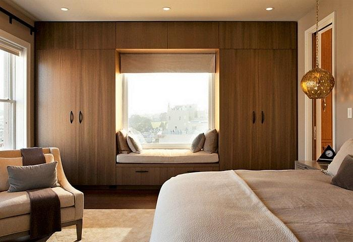 Оформить шкафы во всю стену вокруг окна - удобно и выгодно, вы получите много мест для хранения, при этом шкаф сливается со стеной, а у окна появляется дополнительное место для отдыха