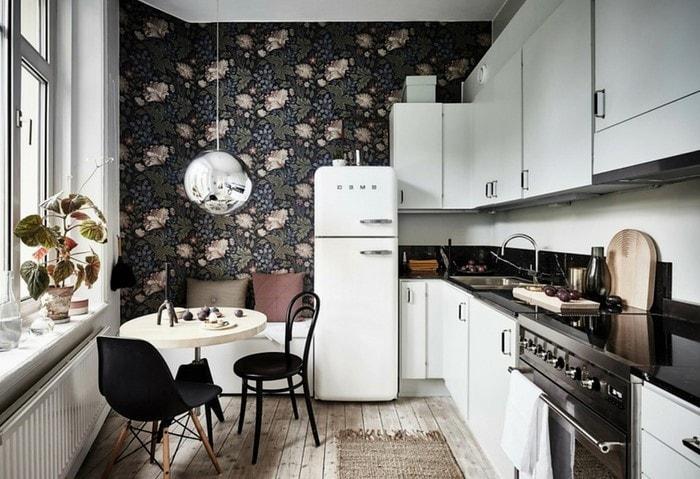 Ремонт маленькой кухни: темные стены с природным орнаментом, контрастный белый гарнитур, небольшой столик