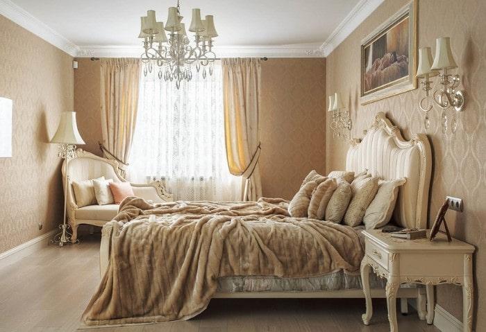 Спальня в классическом стиле, обои с природным орнаментом, массивная люстра на потолке, резная мебель из светлого дерева