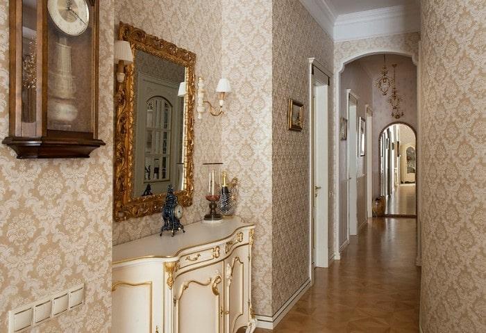 Коридор в классическом стиле, зеркало в толстой раме с характерными цветочными мотивами, резная мебель