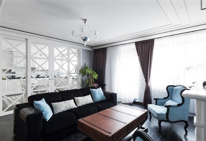 Светлая гостиная в современном классическом стиле, обилие естественного света, прозрачная перегородка на кухню и резная мебель нежно-голубой обивки придают комнате воздуха