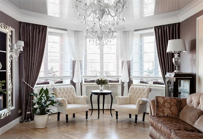 Строгая гостиная в классическом стиле, большие окна дают много естественного света, которые отражает и рассеивает глянцевый потолок, так же классическая хрустальная люстра и дополнительное освещение
