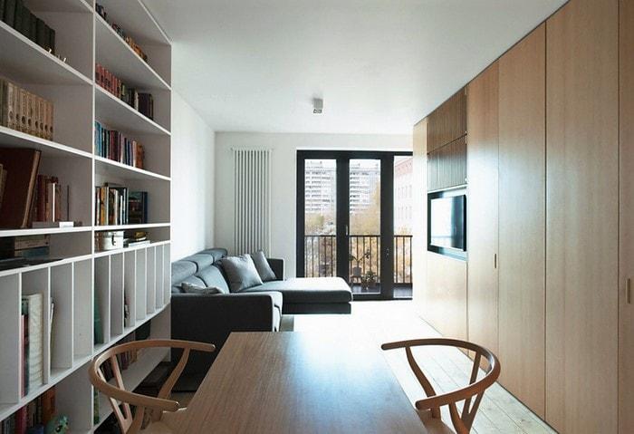 Строгий скандинавский ремонт, практичный деревянный стеллаж во всю стену со встроенным монитором