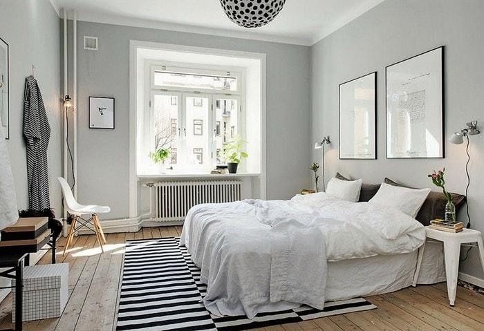 Серый вариант спальни в скандинавском стиле с белыми акцентами и интересным полосатым ковром