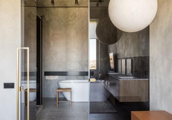 Каменный минимализм в квартире для одного мужчины, стену между спальней и ванной заменили стеклянной перегородкой, таким образом холодный серый смягчается естественным светом