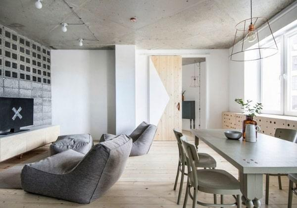 Обилие фактурных поверхностей в минимализме, на фото хорошо видно отличное сочетание дерева, бетона а контрастного серого текстиля