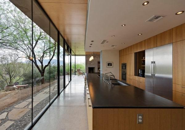 Тёплые минималистичный ремонт загородного дома, фактура натурального дерева отлично сочетается с пейзажем за стеклянными стенами
