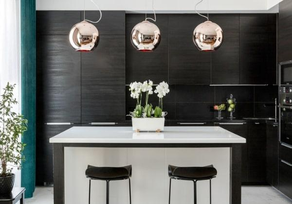 Необычная чёрная кухня в стиле минимализм, характерные хромированные светильники, минималистичные барные стулья с низкими обрезанными спинками, несколько живых растений