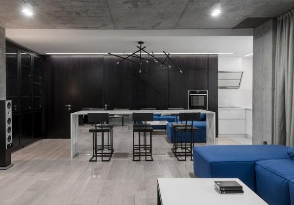 Холодный ремонт в стиле минимализм с объединёнными комнатами и интересным зонированием цветами: чёрный - зона кухни и готовки, синий - зона гостиной, между ними светлый стол с черными барными стульями - пограничная обеденная зона