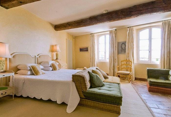 Просторная спальня в стиле Прованс, балки на потолке, обилие тёплых цветов и мягких поверхностей, контрастные зелёные диванчики