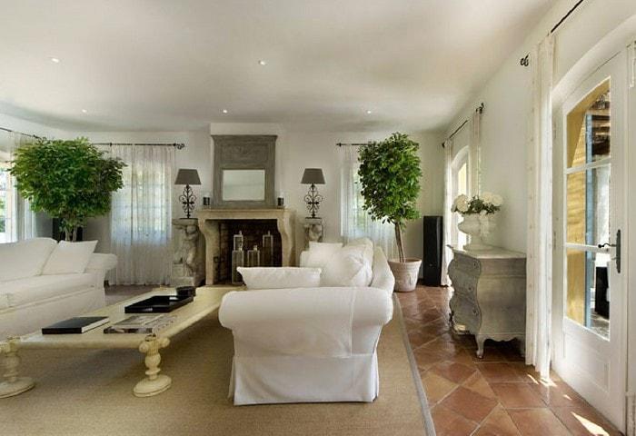 Тёмная состаренная плитка на полу, большой ковёр и белая контрастная мебель