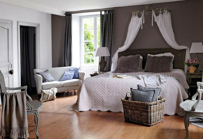 Строгий ремонт спальни в стиле Прованс, белые стены разбавлены контрастной тёмной, сочетающейся со шторами и подушками на кровати